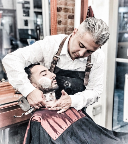 Head Barber Arthur shaving a client with a straight razor - the ultimate close shaving experience