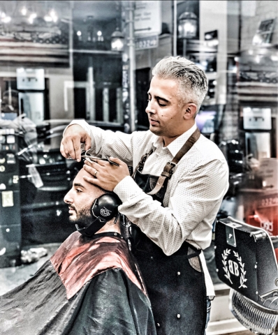 Picture shows head barber at Barber's Blueprint in NYC giving a haircut to a seated client with special ear covers for a sensory inclusive haircut.